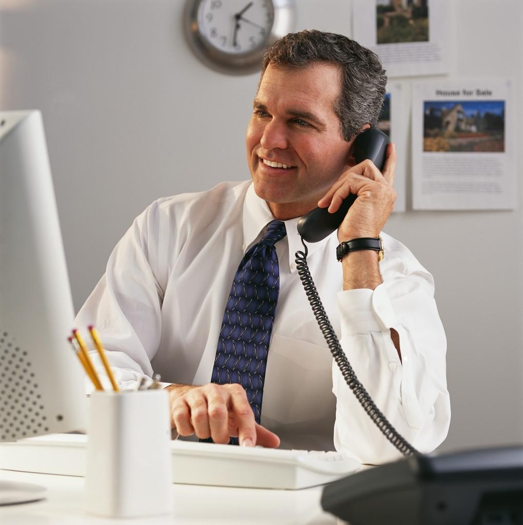 Businessman on Phone While Using Computer